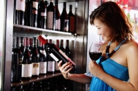 Young woman holding wine glass, reading label on a bottle of wine - Alex Microstock02