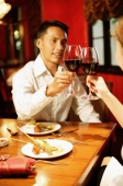 Couple toasting with wine at restaurant - Alex Microstock02