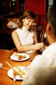 Couple toasting with wine at restaurant, over the shoulder view - Alex Microstock02