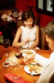 Couple at restaurant, eating, over the shoulder view - Alex Microstock02
