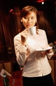 Woman holding cup and saucer, looking away - Alex Microstock02