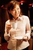 Woman holding cup and saucer, looking away, smiling - Alex Microstock02
