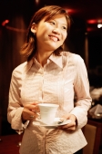 Woman holding cup and saucer, smiling - Alex Microstock02