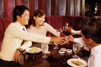 Couples sitting at restaurant, toasting with drinks across table - Alex Microstock02