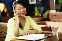 Young woman sitting at table, notebook open in front of her, using mobile phone - Alex Microstock02
