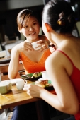 Young women at cafe, having coffee, over the shoulder view - Alex Microstock02