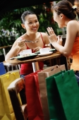 Young women at cafe, talking over coffee, shopping bags behind them - Alex Microstock02
