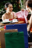 Young women at cafe, one showing items from shopping bag - Alex Microstock02