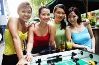 Young women posing next to foosball table - Alex Microstock02