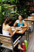 Young women at cafe, eating and drinking - Alex Microstock02