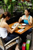 Two women at cafe, having coffee and food - Alex Microstock02