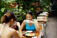 Two women sitting at table, having coffee and fruits - Alex Microstock02