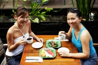 Two women sitting at table, having coffee and fruits, looking up at camera - Alex Microstock02