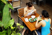 Two women at cafe, having coffee and food, high angle view - Alex Microstock02