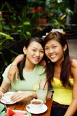 Two women, one with arm around the other, looking at camera - Alex Microstock02