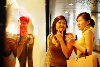 Young women looking at window display, talking - Alex Microstock02