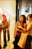 Young women window shopping, standing outside window display - Alex Microstock02
