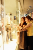 Young women, standing outside window display, looking in, pointing - Alex Microstock02