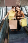 Young women, standing on escalator, looking up at camera - Alex Microstock02