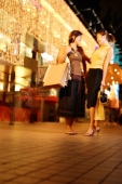 Young women standing side by side, carrying shopping bags - Alex Microstock02
