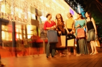 Young women standing side by side, in a row, carrying shopping bags - Alex Microstock02