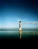 Asian female walking along edge of horizon pool - Martin Westlake