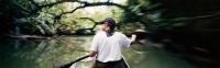 Caucasian male paddling dugout canoe - Martin Westlake