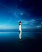 Asian female standing along edge of horizon pool - Martin Westlake