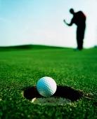 Asian golfer putting ball in hole - Martin Westlake