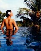 Asian female relaxing in pool - Martin Westlake