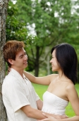 Couple leaning on tree, embracing, looking at each other - Alex Microstock02