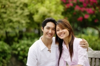 Couple sitting on park bench, smiling at camera - Alex Microstock02