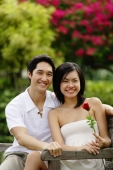 Couple sitting on park bench, looking at camera, woman holding rose - Alex Microstock02