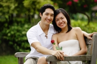 Couple sitting on park bench, smiling at camera, woman holding rose - Alex Microstock02
