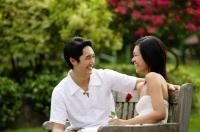 Couple sitting on park bench, looking at each other, woman holding rose - Alex Microstock02