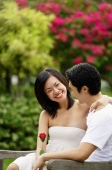 Couple sitting on park bench, looking at each other - Alex Microstock02