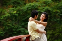 Couple standing face to face on bridge, woman with arms around mans neck - Alex Microstock02