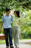 Couple walking in park, man carrying picnic basket - Alex Microstock02