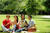 Young adults having picnic in park, looking at camera - Alex Microstock02
