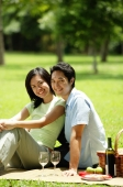 Couple having picnic in park, looking at camera - Alex Microstock02