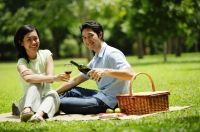 Couple in park, man pouring wine for woman, both looking at camera - Alex Microstock02