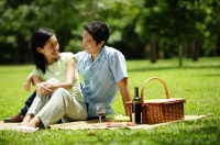 Couple in park, sitting with picnic basket, portrait - Alex Microstock02