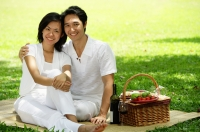 Couple in park, sitting with picnic basket, smiling at camera - Alex Microstock02