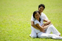 Couple embracing, sitting on grass, smiling at camera - Alex Microstock02