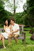 Couple sitting on park bench, woman laughing - Alex Microstock02