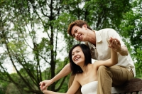 Couple sitting on park bench, man sitting behind woman, holding her hands - Alex Microstock02