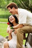 Couple on park bench, woman holding a rose, smiling - Alex Microstock02