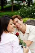 Couple sitting on park bench, woman holding a rose, looking away - Alex Microstock02