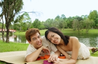 Couple lying on mat in park, looking at camera - Alex Microstock02