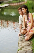 Couple crouching next to pond edge - Alex Microstock02